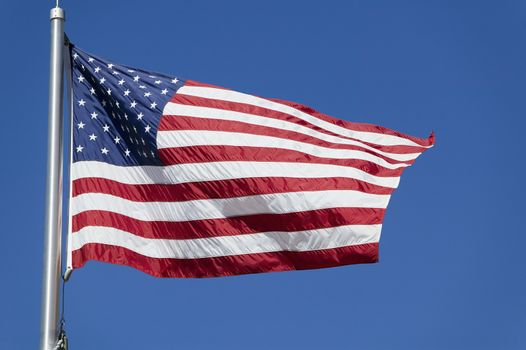 American flag waves in the wind against a blue sky