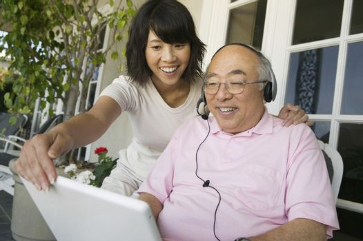 Happy daughter assisting father in using laptop at porch