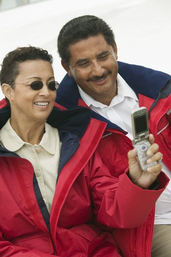 Couple taking a self portrait through cell phone on a yacht