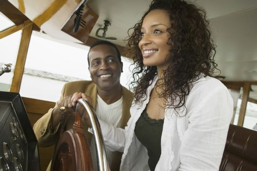 Happy couple at steering wheel of yacht