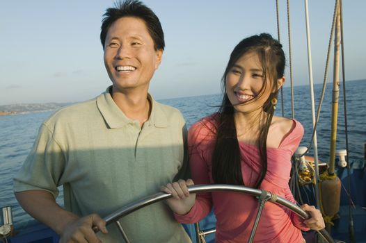 Happy couple standing at the steering wheel on the yacht