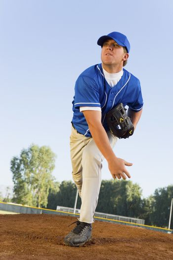 Baseball pitcher on pitcher's mound at full stretch after throwing a shot