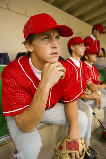 Baseball player watching the game intensely while sitting in dugout with other players