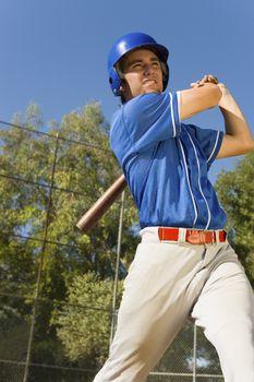 Young male player swinging baseball bat