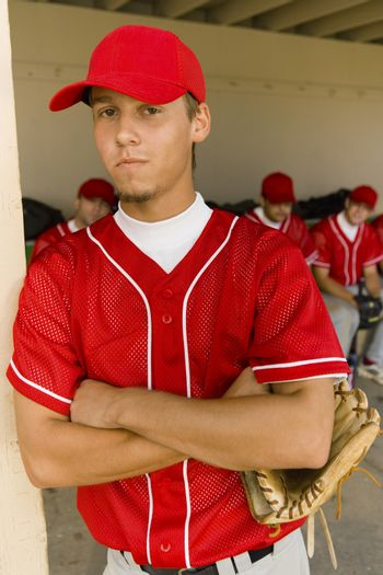 Portrait of a young baseball player with teammates sitting in dugout in background