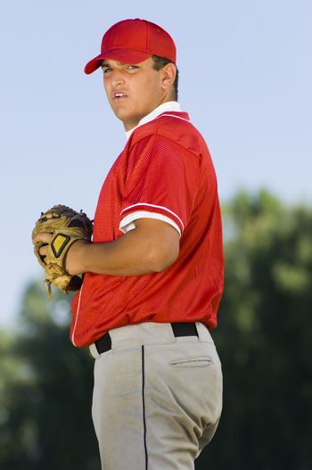 Side view of a young baseball pitcher holding mitt