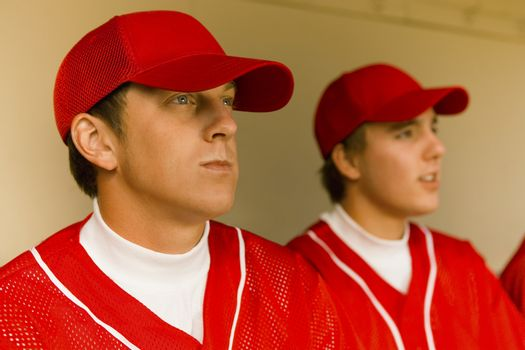Baseball player sitting with team in dugout