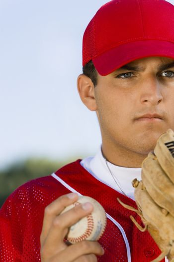 Young baseball pitcher with glove and ball