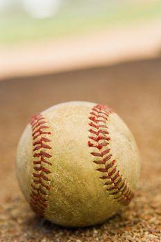 Baseball laying in the base path on a baseball field