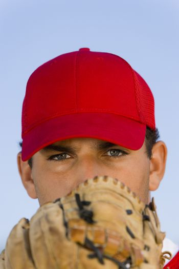 Portrait of baseball pitcher with glove in front of face