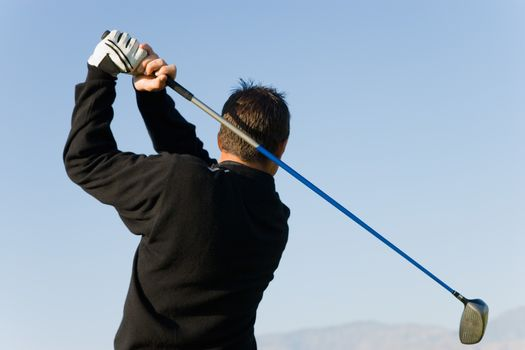 Rear view of a young man swinging golf club