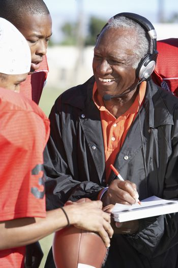 Senior African American coach with rugby players noting down score in book