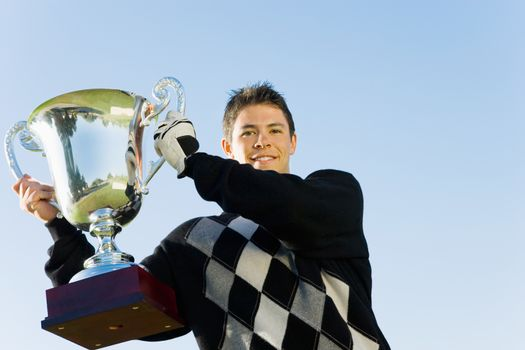 Portrait of happy young man holding trophy against clear sky