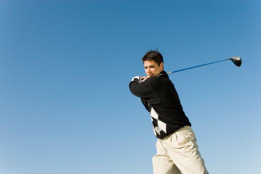 Young man swinging golf club against clear sky