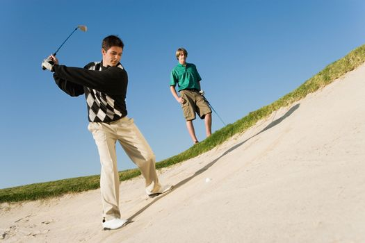 Young man chipping golf ball out of a sand trap with competitor in background