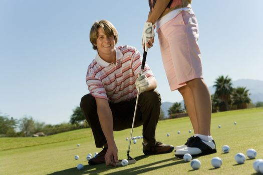 Portrait of a happy young man teaching woman to play golf