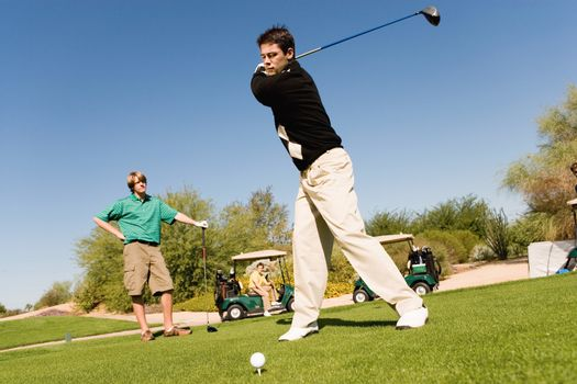 Full length of young Caucasian friends playing golf at golf course
