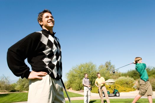 Three male golfers watching other golfer teeing off