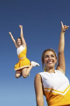 Ecstatic female cheerleaders against clear sky