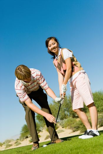 Portrait of a happy young woman learning golf from man on golf course