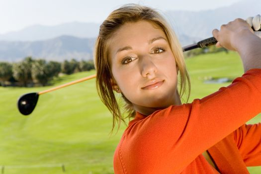 Close-up of a young woman swinging club on golf course