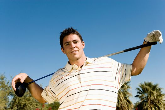 Portrait of a confident young man with golf club against clear sky and trees
