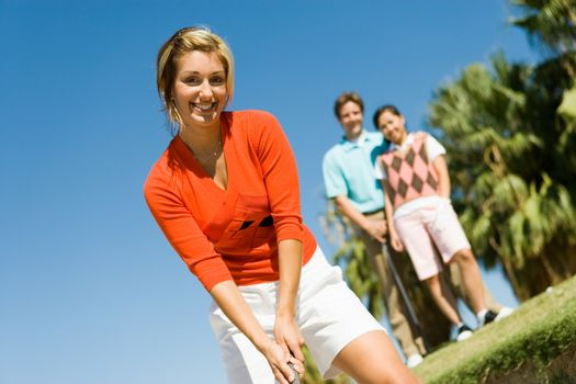 Portrait of happy young woman playing golf with friends in background