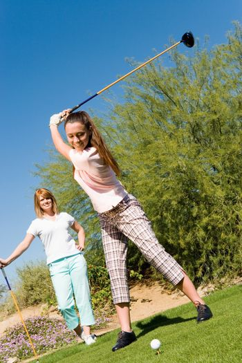 Happy young woman playing golf with female competitor in background