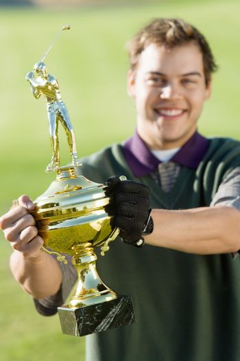 Portrait of a cheerful middle aged man holding golf trophy