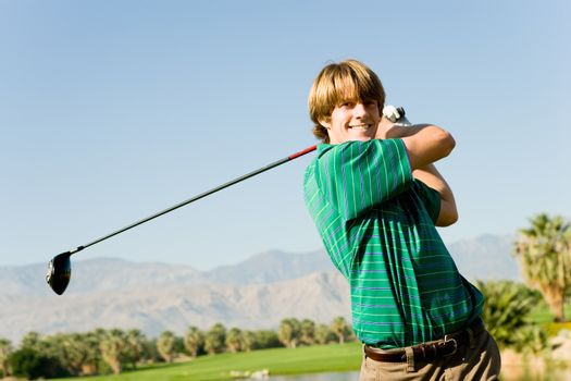 Portrait of a happy young man swinging club at golf course