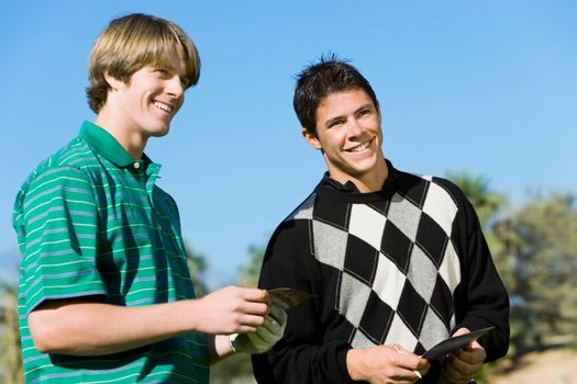 Two smiling male golfers standing next to each other against clear blue sky