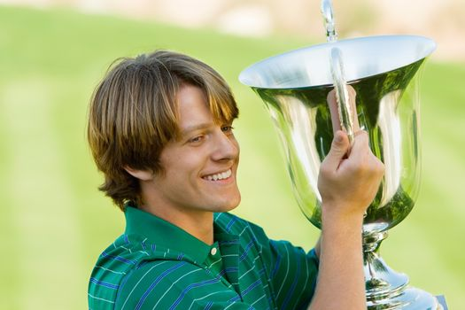 Happy young male golfer holding his winning trophy