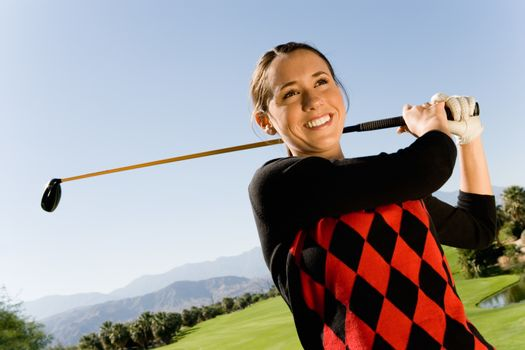 Happy young woman swinging club on golf course with mountains in background
