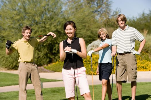 Group of four friends holding golf clubs on golf course