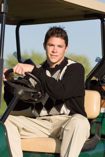 Portrait of a young man driving golf cart