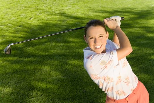 High angle view of a happy young woman playing golf