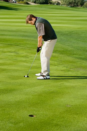 Full length of a man concentrating on making putt on golf course