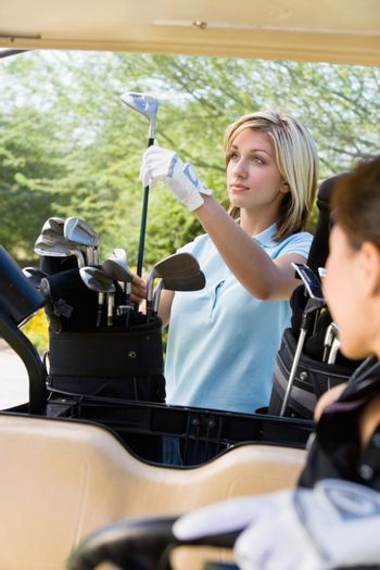Beautiful young woman selecting golf club from bag with friend in foreground