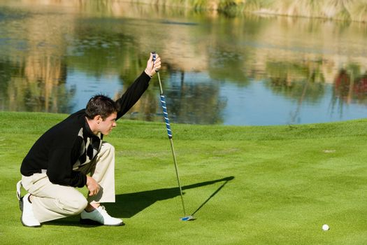 Full length of a young male golfer lining up putt nearby lake