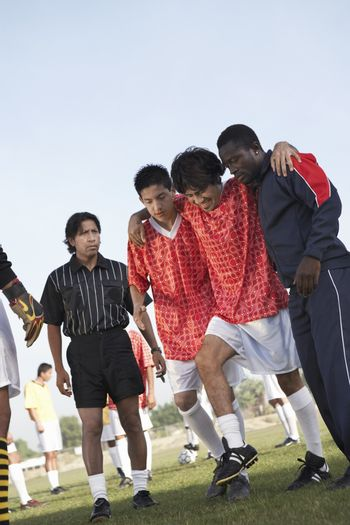 Team-mates carrying injured soccer player