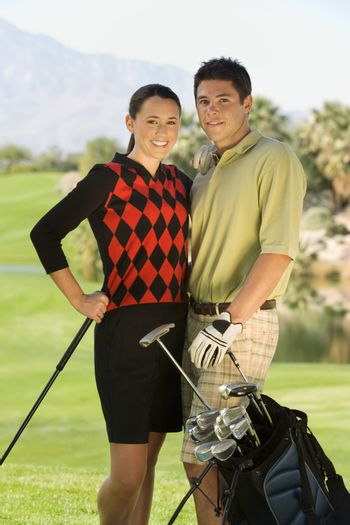 Portrait of a smiling golf couple standing together with golf bag on course