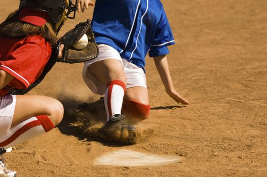 Female baseball player sliding into base with baseman in the foreground