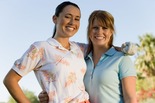 Portrait of happy female friends standing with arm around on golf course