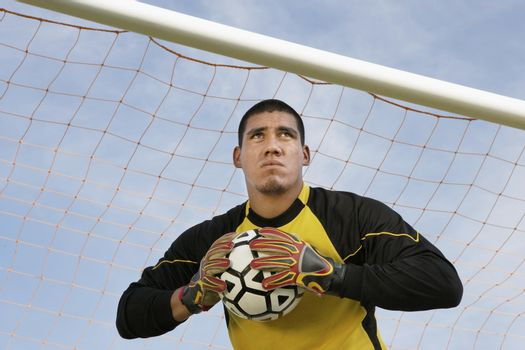 Low angle view of a goalkeeper holding a ball