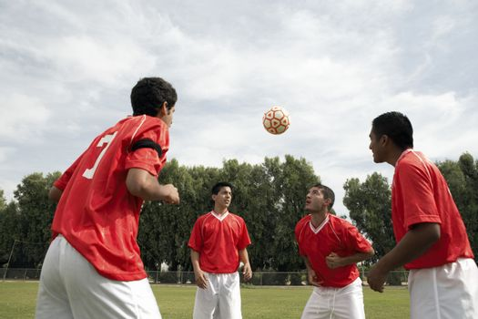 Footballers heading the ball during a practice session