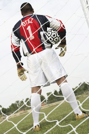 Rear view of a goalkeeper standing with the ball on the field