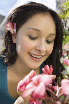 Closeup of a beautiful young woman looking at flowers at botanical garden