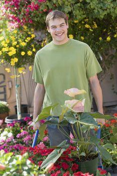 Portrait of a happy man gardening with a wheelbarrow at botanical garden