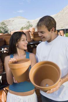 Happy couple buying pots at botanical garden