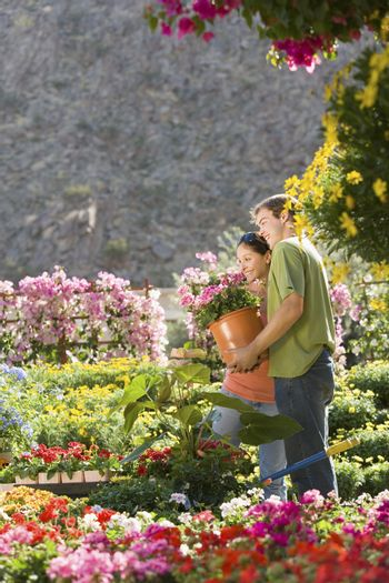 Happy couple buying potted plant at botanical garden